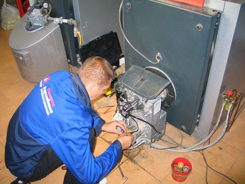 мастер ремонтирует напольный газовый котел